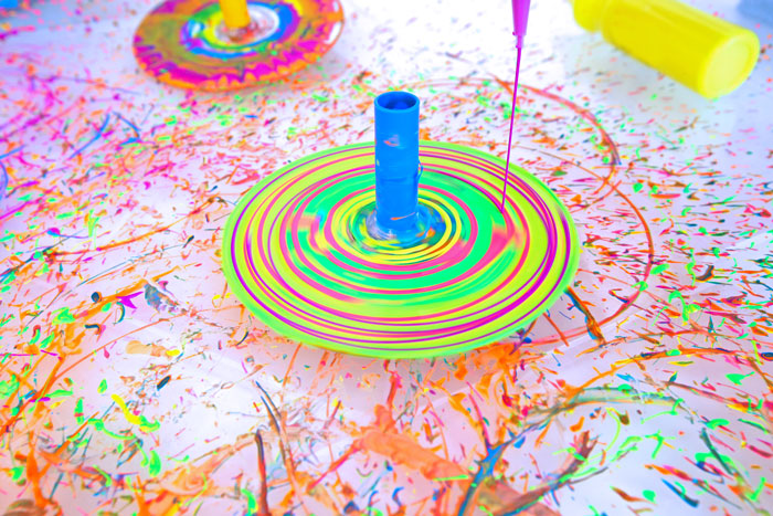 "Make spin art using DIY tops! Great STEAM project for preschoolers from the new book ""STEAM Play & Learn"" by Ana Dziengel of Babble Dabble Do"