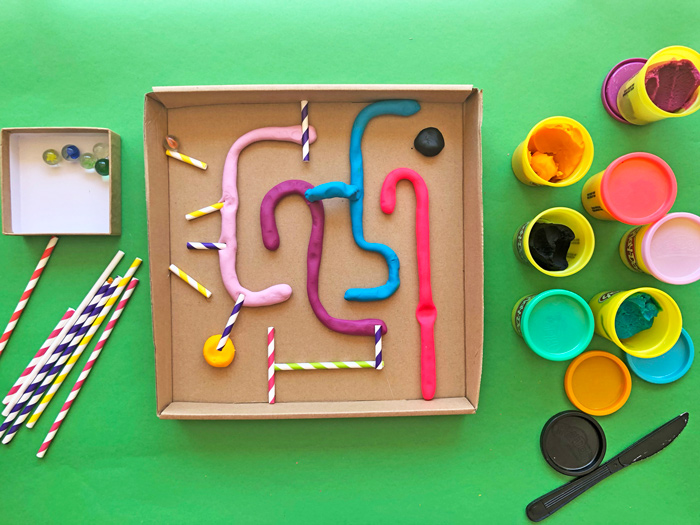 """Create a simple DIY marble maze using play dough """"snakes"""" and a box lid. Learn about design and problem solving with this DIY toy."""